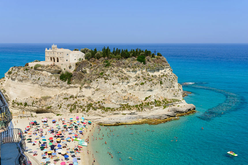 "Beli pesak, slikovite stene i kristalno čista voda | <em>Creative Commons - image by <a href=""https://commons.wikimedia.org/wiki/File:Santa_Maria_dell'Isola_-_Tropea_-_Calabria_-_Italy_-_July_17th_2013_-_03.jpg"" target=""_blank"" rel=""nofollow""> Norbert Nagel / commons.wikimedia.org</a></em>"